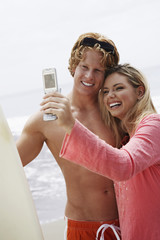 Happy young couple with surfboard taking self-portrait through cell phone on beach