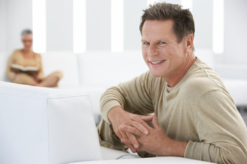 Portrait of smiling man with hands clasped with woman in background at home