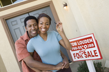 Portrait of a cheerful African American couple with keys of their new house
