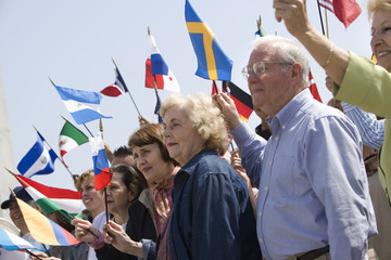 Multiethnic people raising flags of different countries against clear sky