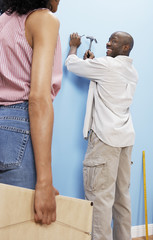 African American couple hammering nail into wall to hang picture frame