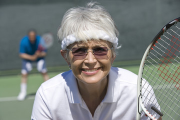 Portrait of happy senior woman playing tennis
