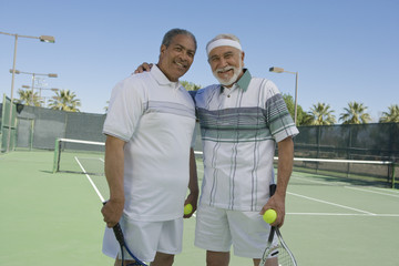 Portrait of happy senior male friends standing with arm around at tennis court