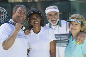 Portrait of happy senior friends in sportswear at tennis court