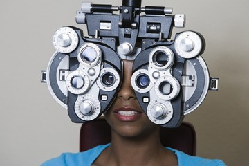 An African American woman having her vision checked with a Phoropter over grey background