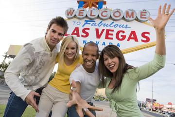 Portrait of playful friends standing together against 'Welcome To Las Vegas' sign