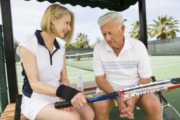Senior Caucasian couple relaxing on bench after playing tennis