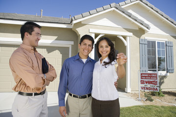 Portrait of happy couple holding house key with estate agent standing besides
