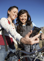 Two female bicyclists photographing themselves with digital camera against the blue sky