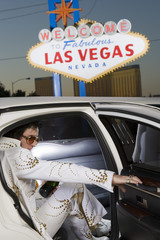 Elvis Presley impersonator stepping out from car with 'Welcome To Las Vegas' sign in the background