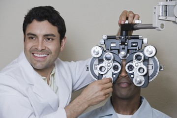 Happy male optometrist adjusting panels of phoropter while examining patient over grey background