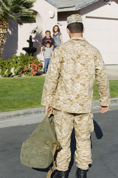Rear view of army soldier returning home with family waiting in background