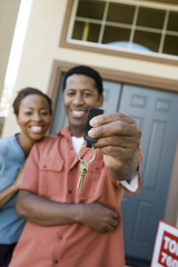 Happy African American couple holding a pair of keys of their new house