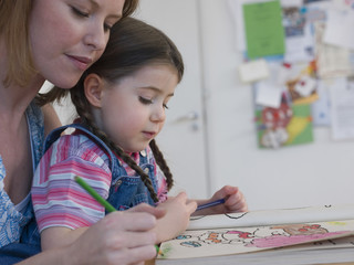 Mother and daughter coloring together at home