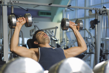 Selective focus of man lifting weights at a gym