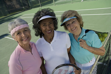 Three female senior tennis players in court smiling