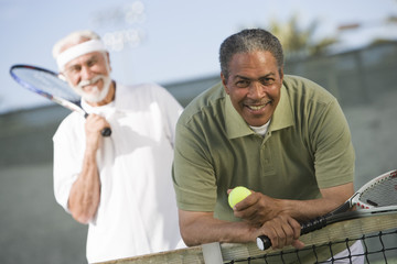 Portrait of senior African American man with friend playing doubles