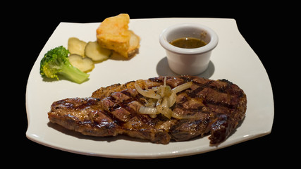 Rib eye steak isolated on black background.