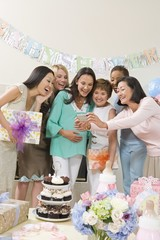Happy Pregnant woman with diverse friends looking at camera at baby shower