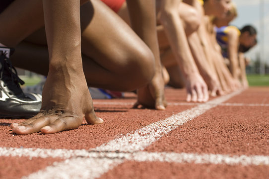 Cropped image on diverse athletes at starting line ready to race