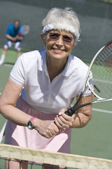Happy senior woman playing tennis in court