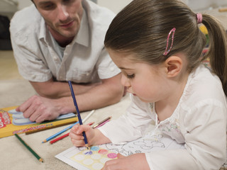 Cute little girl coloring pictures with father looking at it on floor