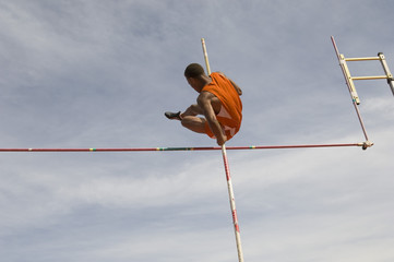 Low angle view of male pole vaulter clearing bar against cloudy sky