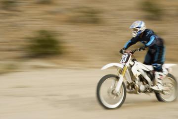 Full length of a male road biker riding motor bike