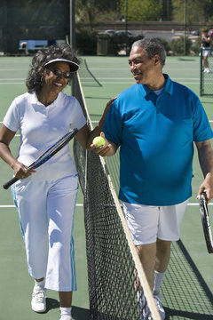 Happy African American couple playing together on tennis court