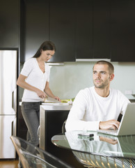 Thoughtful young man using laptop with woman preparing food in kitchen