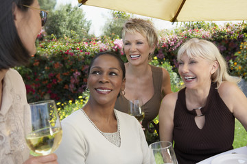 Four cheerful multiethnic middle aged women chatting with wine glasses at the garden party