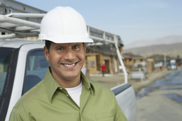 Portrait of a smiling construction worker in hardhat standing next to truck on construction site