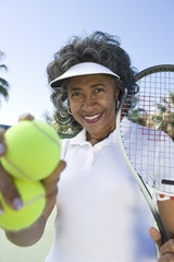 Portrait of a happy senior female tennis player holding racquet and balls