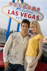 Happy couple standing together with car and 'Welcome To Las Vegas' sign in the background