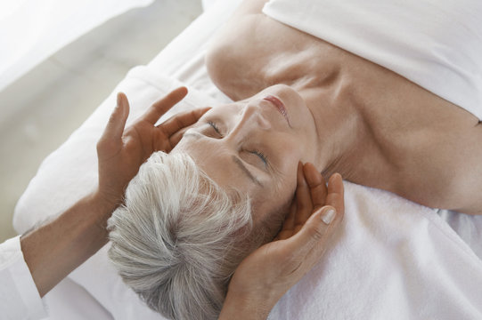 Closeup of a senior woman receiving massage at spa