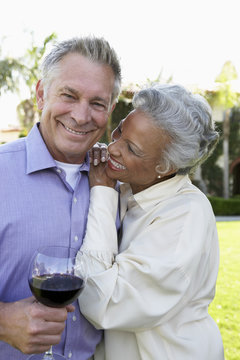 Happy multiethnic couple standing together while man holding wine glass at lawn