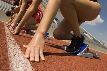 Cropped image of runners preparing for race at starting blocks