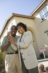 Portrait of happy senior couple holding key in front of new house