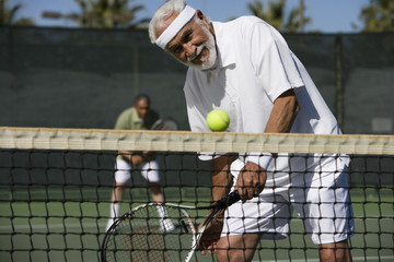 Happy senior man playing doubles on tennis court