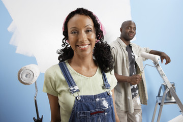 Portrait of a beautiful African American woman with man painting new house