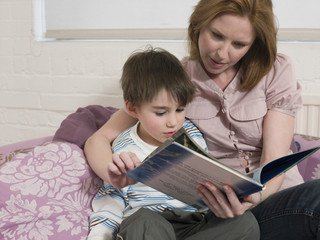 Young woman and cute son with picture book looking at each other in house