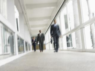 Blurred motion of multiethnic businessmen walking in office corridor