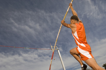 Male pole vaulter taking off in sports field