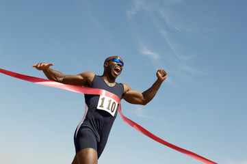 Low angle view of an African American male runner winning race against blue sky Wall mural