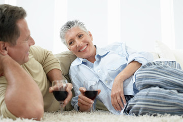 Happy mature couple having red wine on rug at home