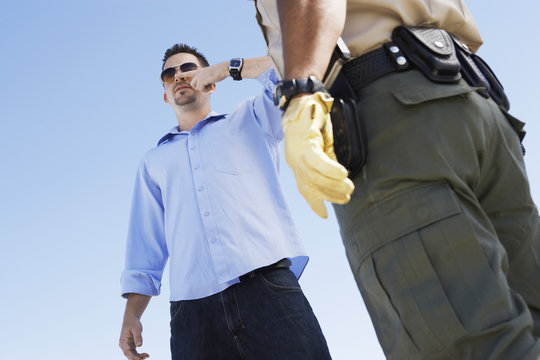 Middle aged man forced to take a field sobriety test by a police officer
