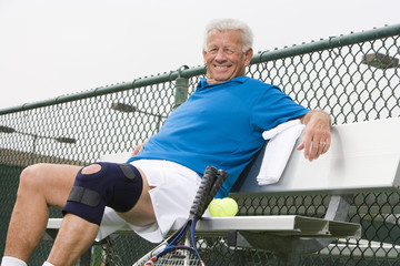 Portrait of a happy senior man relaxing on bench after playing tennis