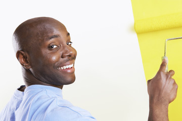 Portrait of a happy African American man painting yellow color on wall