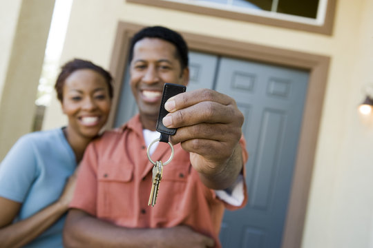 Happy African American couple showing a pair of keys of their new house