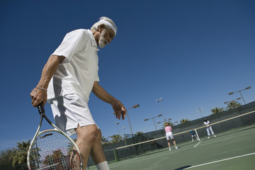 Senior man playing doubles at tennis court